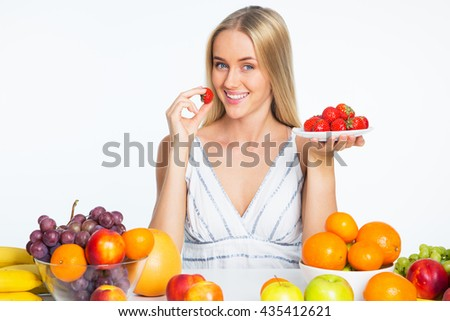Smiling pretty young woman eating strawberries - stock photo