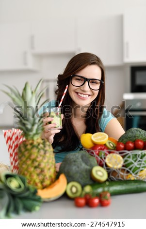 Smiling Pretty Young Woman Wearing Eyeglasses Holding a Glass of Juice at the Table with Fresh Fruits on Top. - stock photo