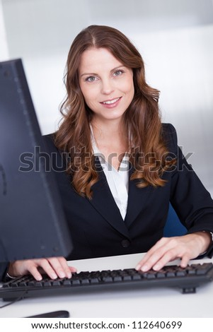 Smiling professional business secretary or personal assistant working at her computer typing on the keyboard - stock photo