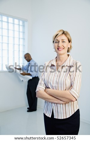 Smiling professional businesswoman standing as man reads architectural plans in background. - stock photo