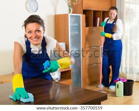 Smiling professional cleaners in uniform cleaning at the living room