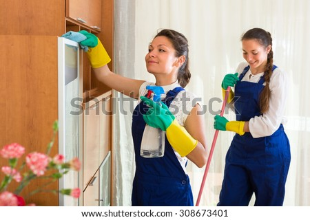Smiling professional cleaners team cleaning in the house with rags and mop. Selective focus - stock photo