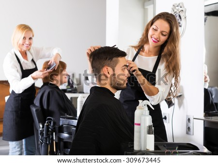 Smiling professional hairdresser doing hairstyle for young men - stock photo
