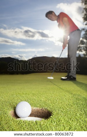 Smiling professional male golf player putting successfully ball on green with close up of ball dropping into cup. - stock photo