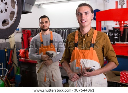 Smiling professional workers in workwear at workshop. Selective focus - stock photo