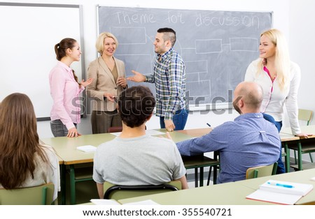 Smiling professionals and happy female coach at training session for employees - stock photo