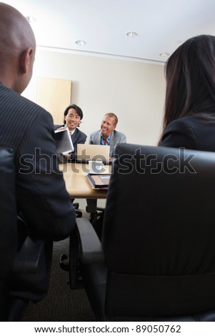 Smiling professionals in a business meeting - stock photo