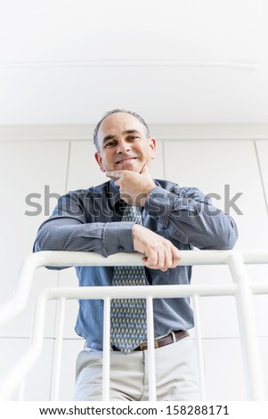 Smiling proud business man standing in office hallway leaning on railing shot from below - stock photo