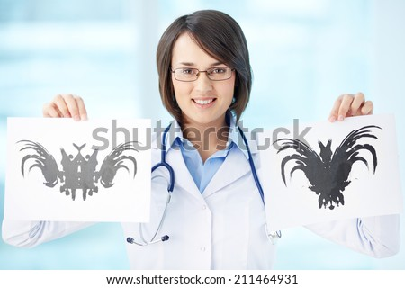 Smiling psychiatrist showing two different pictures - stock photo