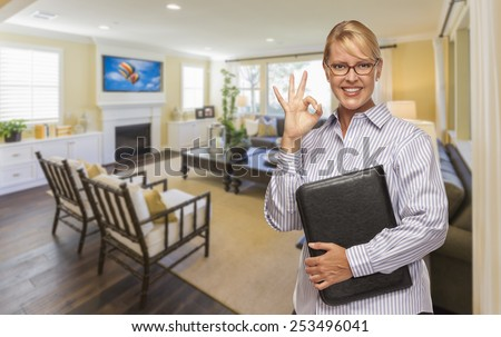 Smiling Real Estate Agent with Okay Sign in Living Room of New House. - stock photo