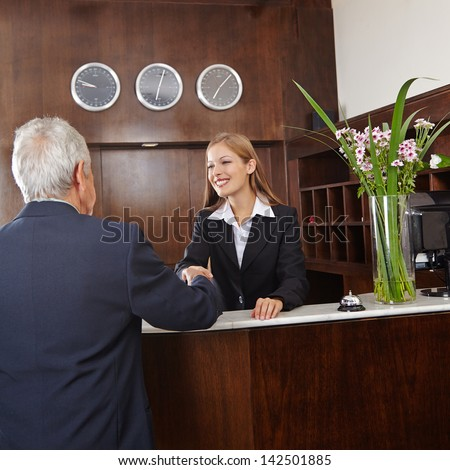 Smiling receptionist in hotel giving handshake to senior guest - stock photo