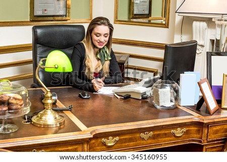 Smiling receptionist making to do list - stock photo