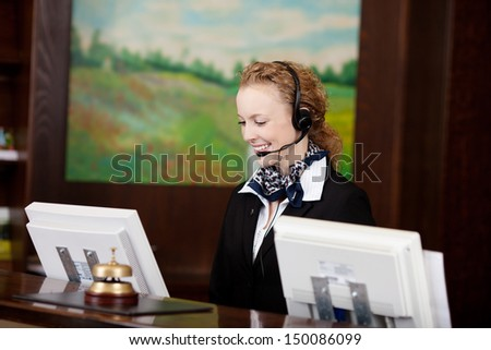 Smiling receptionist wearing a headset working behind a reception counter on her computer as she takes a call from a client - stock photo