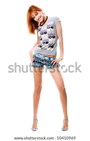 Smiling red-haired girl in a t-shirt and shorts. Isolated on white - stock photo