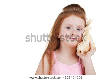 Smiling red-haired little girl in pink swimming suit listens to noise in seashell