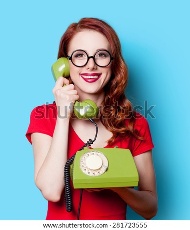 Smiling redhead girl in red dress with green dial phone on blue background. - stock photo