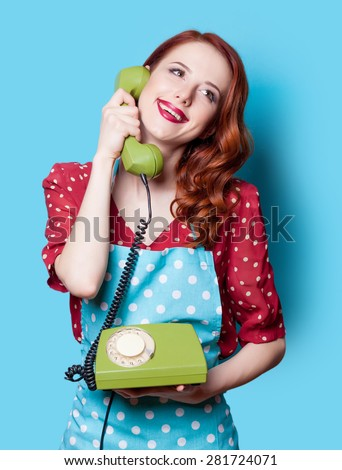 Smiling redhead girl in red polka dot dress with green dial phone on blue background. - stock photo
