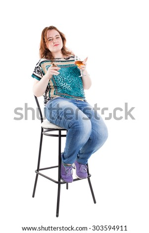 Smiling redhead plus size wreckled model sitting on the bar chair with glass of whiskey and cigar. Studio shot. Isolated on a white background. - stock photo