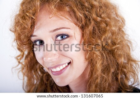 smiling redhead woman looking at the camera with beautiful eyes