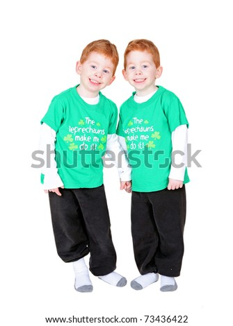 Smiling redheaded twins holding hands isolated on white