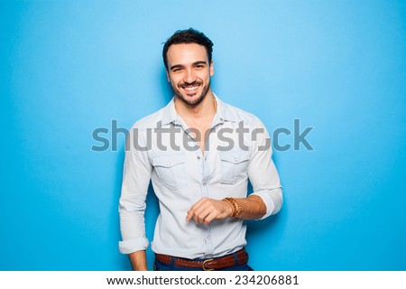 smiling relaxed and confident man on a blue background - stock photo