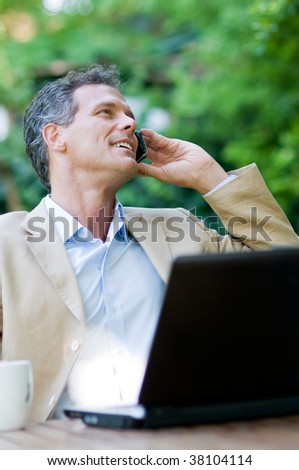 Smiling relaxed businessman talking on mobile outdoor