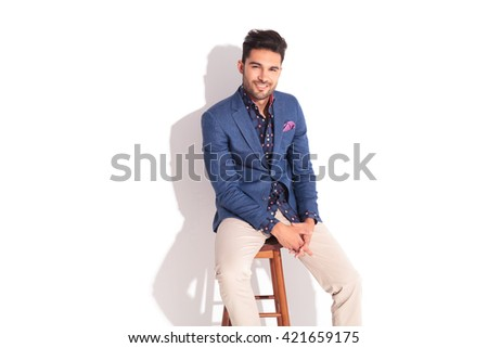 smiling relaxed man in suit sitting on a stool and looks at the camera in studio - stock photo