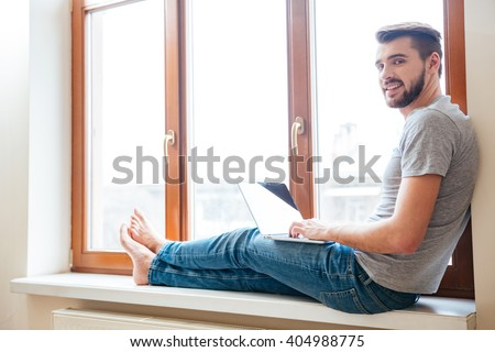 Smiling relaxed young man using laptop sitting on window sill  - stock photo