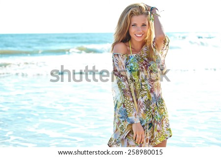 smiling relaxed young woman looking away at the beach - stock photo