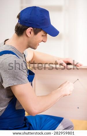 Smiling repairman using repair tools at home interior. - stock photo