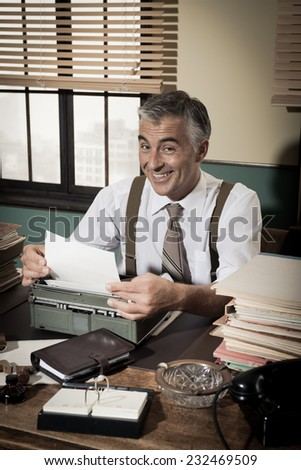 Smiling reporter working at office desk with vintage typewriter, 1950s style. - stock photo