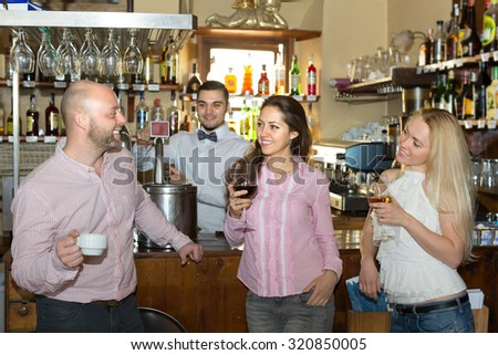 Smiling restaurant guests waiting for table and having beverages at tavern  - stock photo
