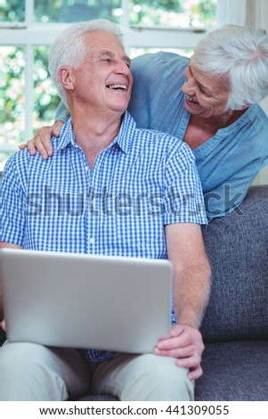 Smiling retired couple using laptop at home - stock photo