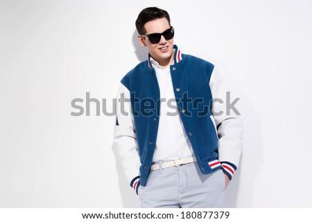 Smiling retro fifties sportive fashion man wearing blue baseball jacket and dark sunglasses. Studio shot against white. - stock photo