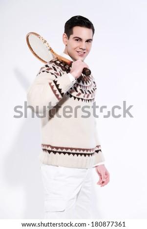 Smiling retro tennis fashion man holding a vintage wooden racket. Studio shot against white. - stock photo