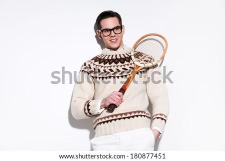 Smiling retro tennis fashion man with black glasses holding a vintage wooden racket. Studio shot against white. - stock photo