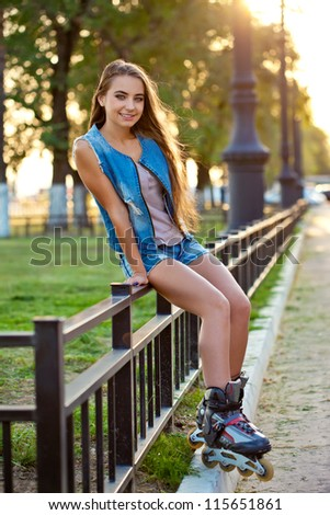 smiling roller girl wearing jeans sitting on iron fence over sunset