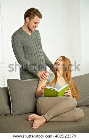 Smiling Romantic Couple With Book Talking on sofa