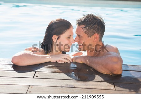 Smiling romantic young couple in swimming pool on a sunny day - stock photo