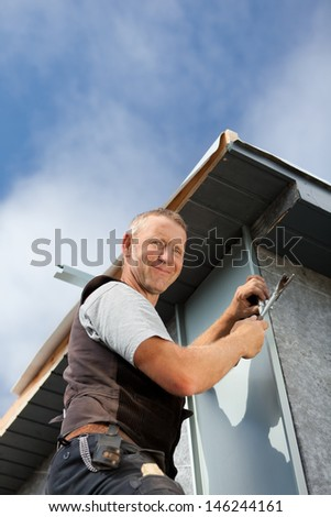 Smiling roofer assembles a metal piece on a dormer wall - stock photo