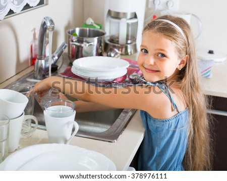 smiling russian female child cleaning dishware at home