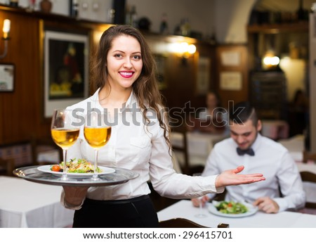 Smiling russian female waiter serving guests table in restaurant - stock photo