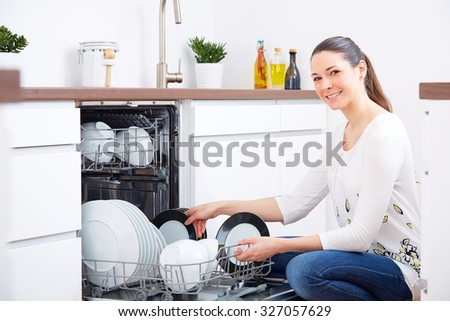 Smiling 20s woman in kitchen, empty out the full dishwasher - stock photo
