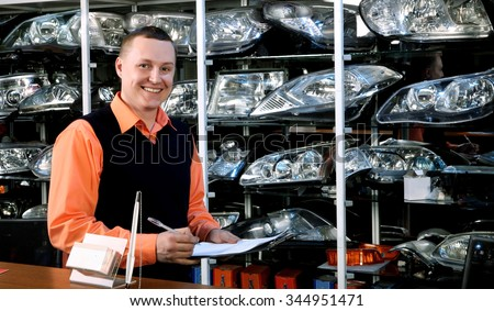Smiling Salesman Auto Parts Store with a Notebook in Hand - stock photo