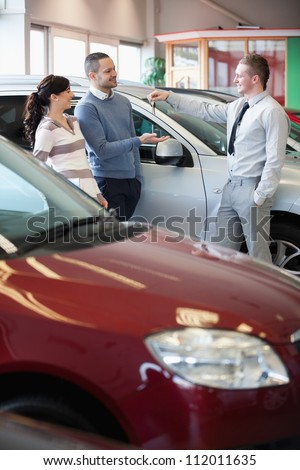 Smiling salesman giving keys to a happy couple in a car shop - stock photo