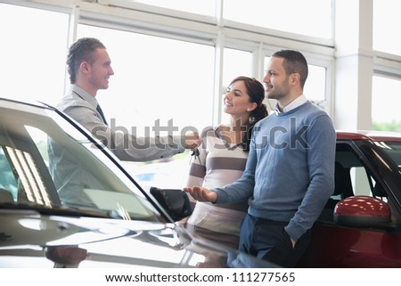 Smiling salesman handing keys to a couple in a car shop - stock photo