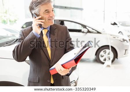 Smiling salesman having a phone call at new car showroom - stock photo