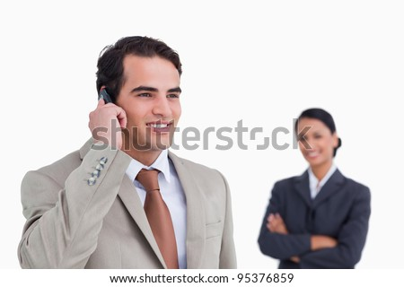 Smiling salesman on his mobile phone with colleague behind him against a white background - stock photo