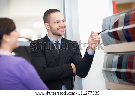 Smiling salesman pointing at a color palette with a woman - stock photo