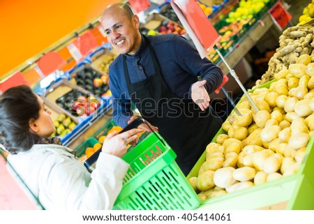 Smiling salesman serving female customer purchasing potatoes in supermarket indoors
